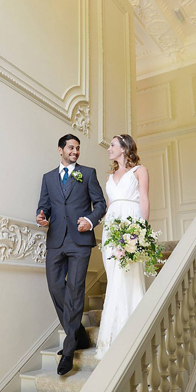 Bride and groom walking down the stairs at Morden Hall