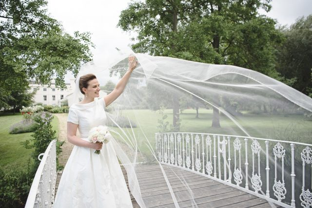 Bride stood on the bridge at a 18th Century wedding venue