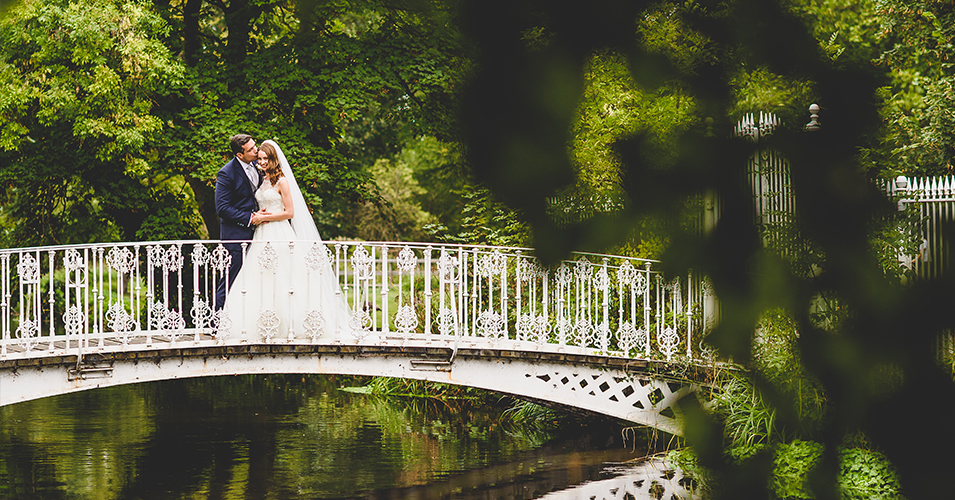 Bride-and-groom-on-the-bridge-at-Morden-Hall-country-house-in-London