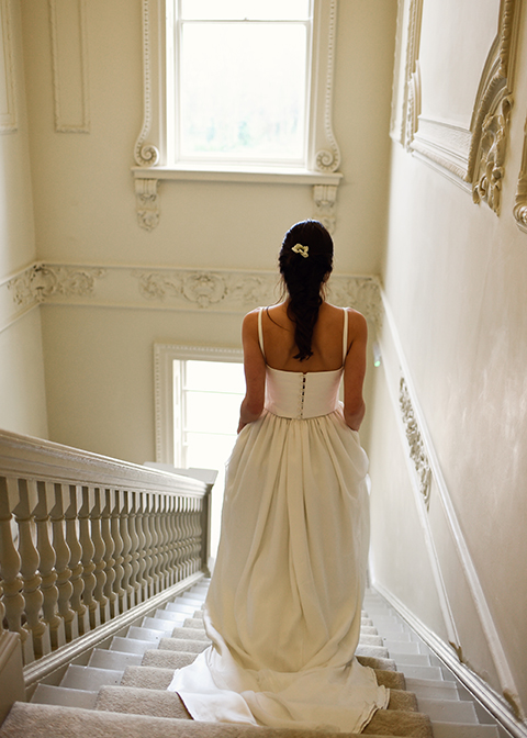 Bride-walking-down-the-stairs-at-Morden-Hall-country-house-in-London