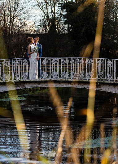 The happy couple take a moment together on the white iron bridge located in the beautiful parkland