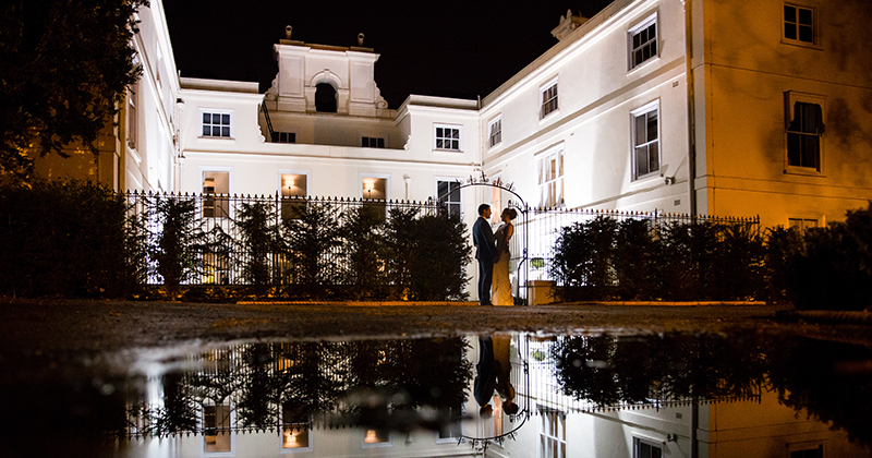 The couple embrace outside of the stunning country house wedding venue which looks beautiful lit up at night