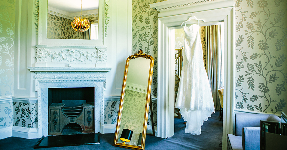 A wedding dress hangs in the stunning and beautifully decorated Cherry room – wedding preparations