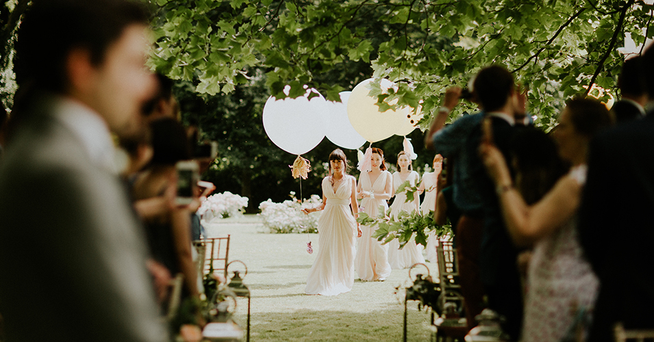 The beautiful bridesmaids wear white floor-length dresses as they make their way along the wedding aisle – outside wedding