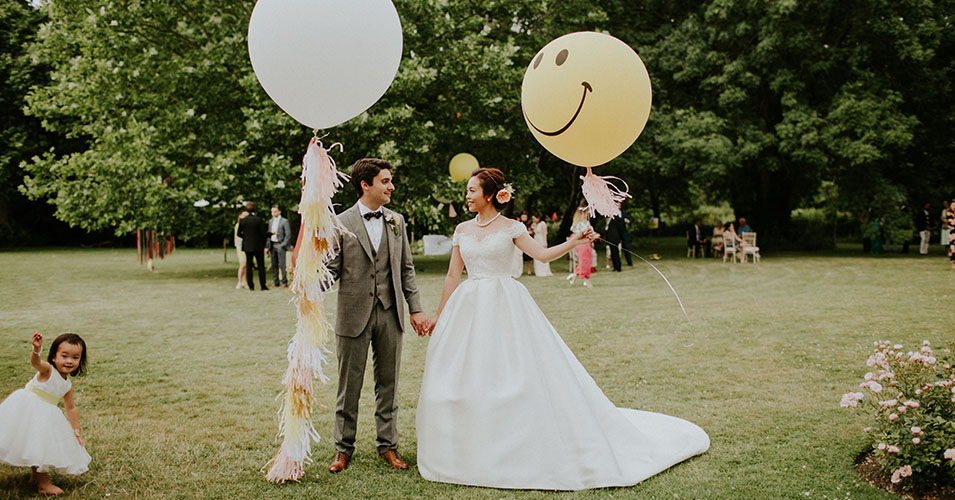 The bride and groom stand in the beautiful gardens holding tasselled oversized wedding balloons