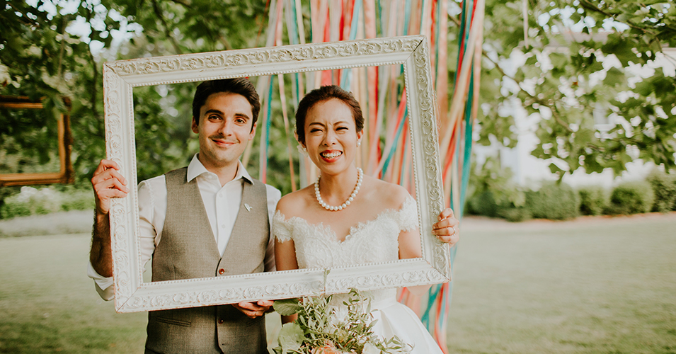 The bride and groom enjoy the photobooth props by smiling for the camera behind a white picture frame