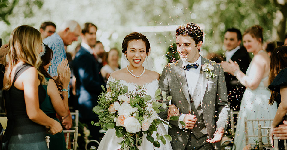 Guests throw wedding confetti over the newlyweds as they leave the outside wedding ceremony