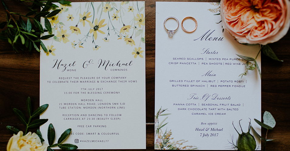 A close up of the couple's elegant wedding invitations surrounded by flowers – wedding stationery