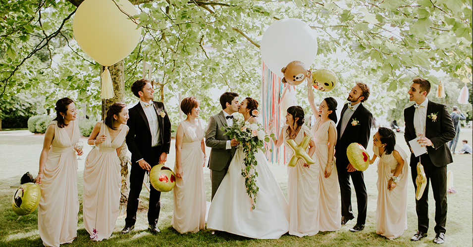 The bride and groom stand with their bridesmaids and groomsmen amongst the trees in the beautiful gardens