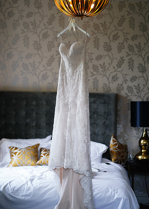 The stunning lace bridal gown hangs in the bridal preparation room at Morden Hall