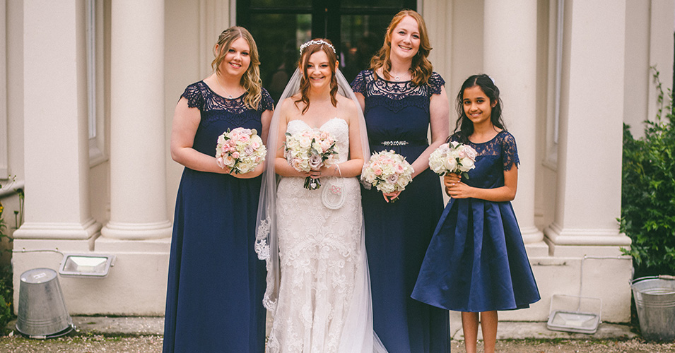 The bride and her bridesmaids wearing navy dresses pose for a photo outside Morden Hall