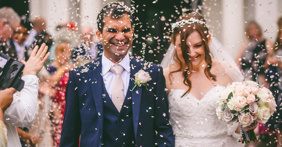 Natural confetti is thrown over the newly married couple at Morden Hall in London