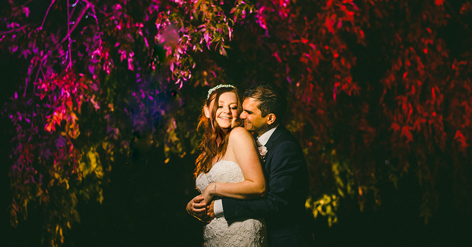 The newly-weds pose for a photo in the beautifully lit trees at Morden Hall