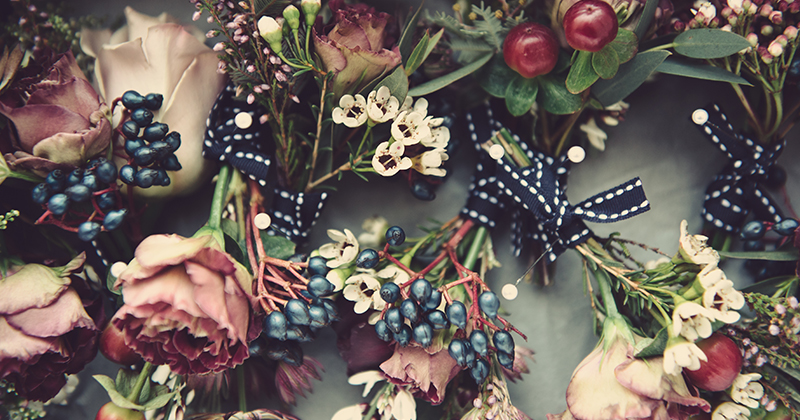 Beautiful deep pink roses and seasonal berries tied with pretty pale flowers make the perfect Autumn wedding button holes