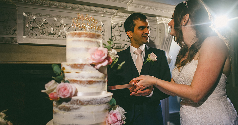 The bride and groom cut the cake at Morden Hall in London