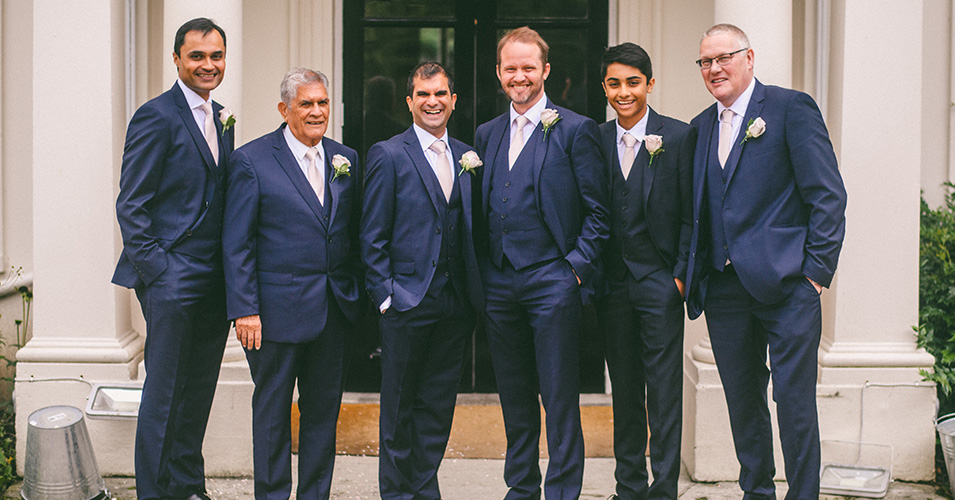 The groom and groomsmen pose for a photo in their navy suits at Morden Hall