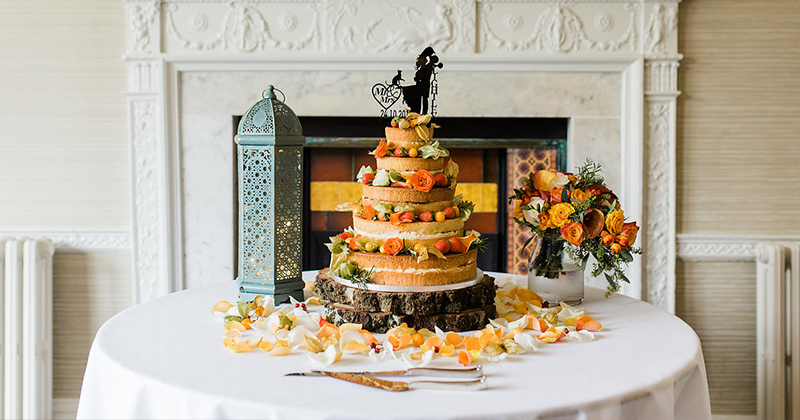 A naked wedding cake decorated with autumnal fruits and flowers is perfect for your autumn wedding at Morden Hall