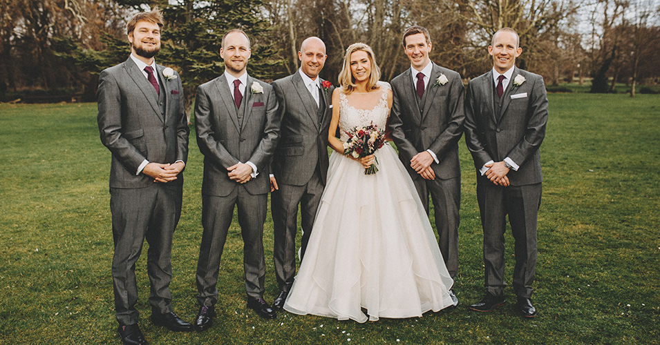 bride-and-groomsmen-marette-and-paul-morden-hall-london Al text: The bride poses with the groom and groomsmen who were wearing grey wedding suits at Morden Hall in London