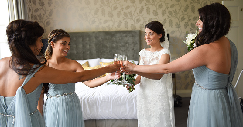 The bridesmaids in pretty pastel blue dresses toast the bride at Morden Hall London
