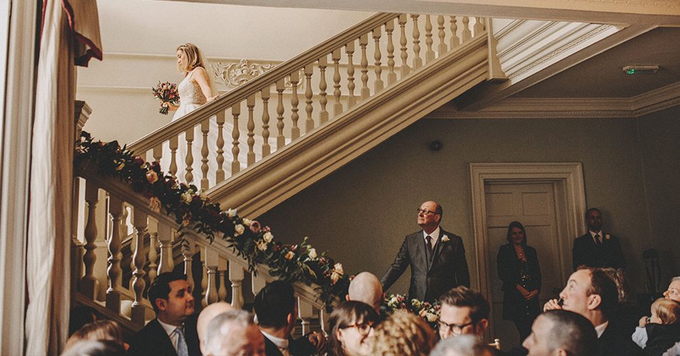 The bride makes a grand entrance as she walks down the stairs to the wedding aisle at Morden Hall London