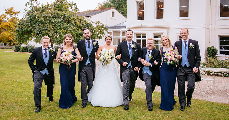 The bride and groom have group wedding photos taken outside of this wedding venue in London