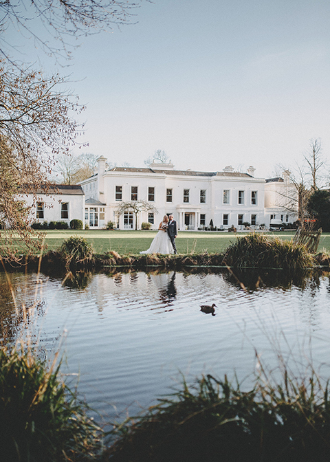 The bride and groom have their photo taken by the River Wandle at Morden Hall in London