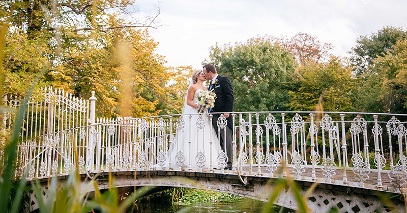 The happy newlyweds pose for wedding photos on the bridge at this London wedding venue