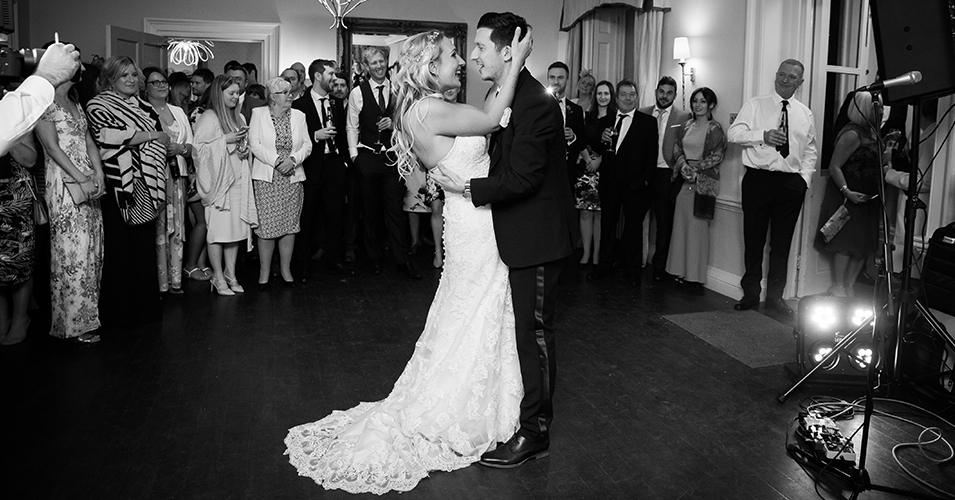 The happy couple take to the floor for their first dance as their wedding guests look on at Morden Hall in London