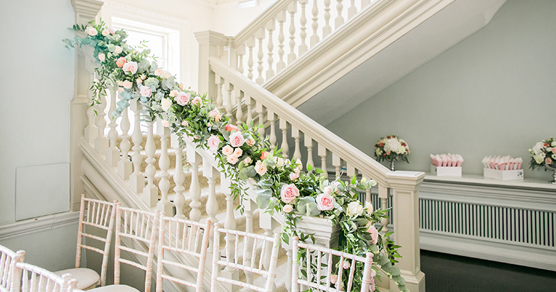The staircase was decorated with a stunning floral garland of pale pink roses and foliage at this wedding at Morden Hall in London