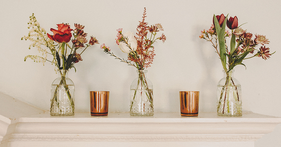 Delicate spring flowers in pretty jars were used to decorate the wedding venue in London