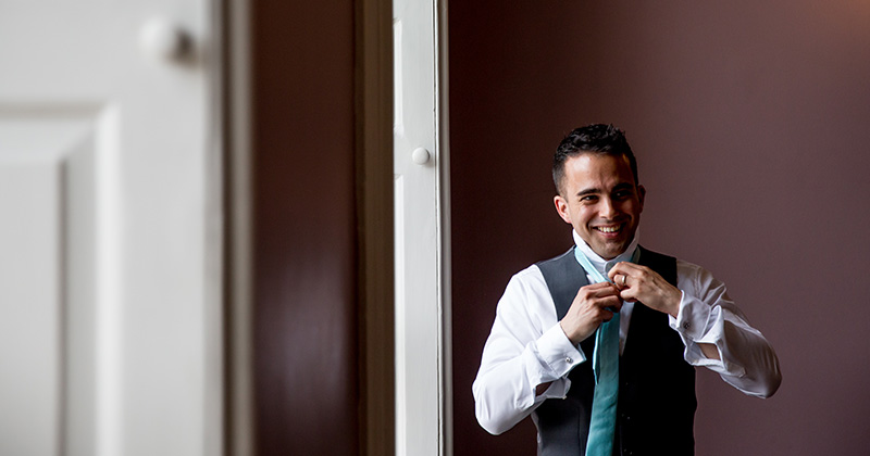 The photographer captures the groom preparing for the wedding in this wedding photo at Morden Hall London