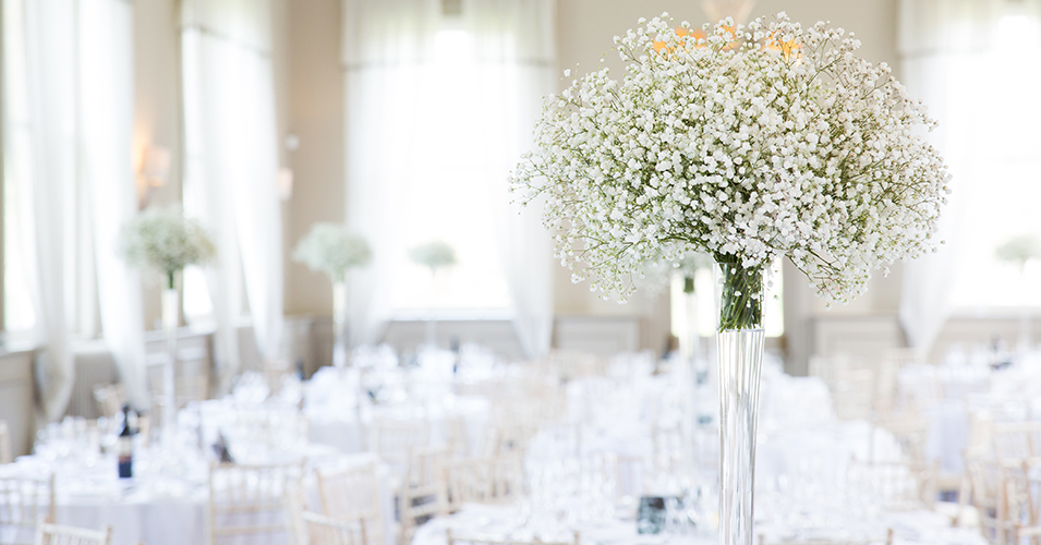 Large bunches of pretty white gypsophila were used as elegant table centrepieces at this wedding reception in London