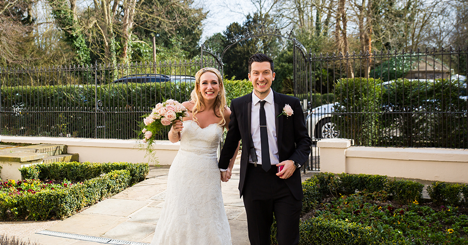 The happy newlyweds pose for a wedding photo at the gates of this country house wedding venue in London
