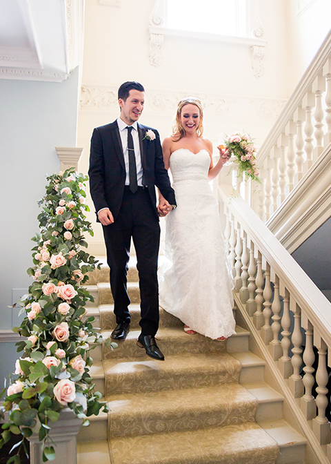 The happy couple walk down the beautifully decorated staircase and make a grand entrance to the wedding reception at this London wedding venue.