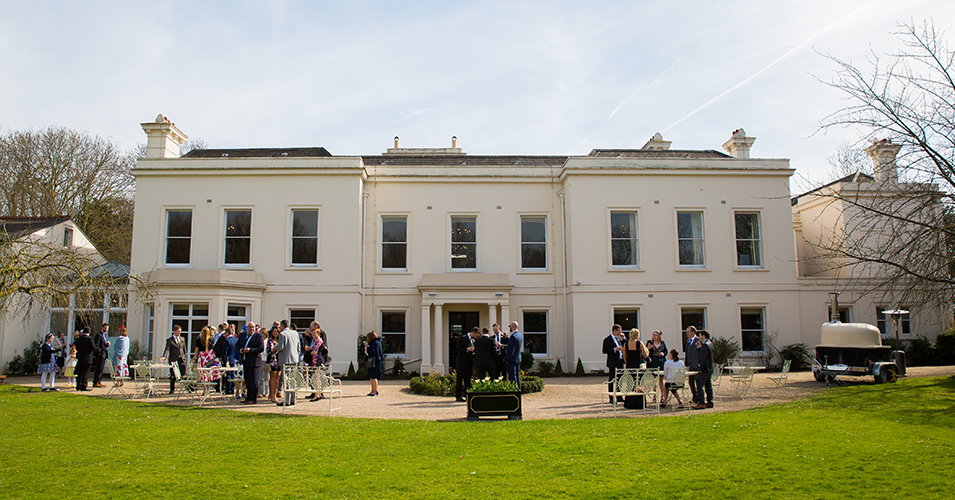 The wedding guests enjoy mingling in the sunshine before the wedding ceremony at Morden Hall in London