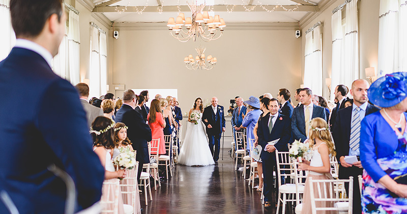 The bride walks down the aisle as her husband and wedding guests look on at Morden Hall in London