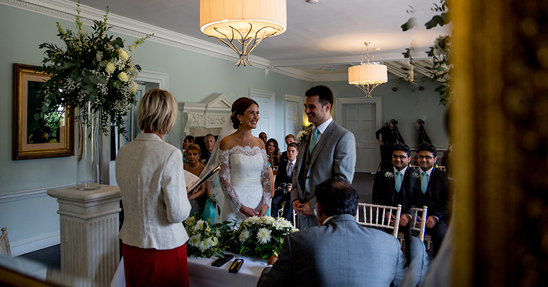 The happy bride and groom say their vows at their wedding ceremony at Morden Hall in London