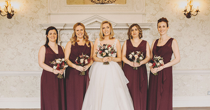 The bridesmaids wear rich burgundy dresses with deep red and white floral bouquets at this winter wedding at Morden Hall in London