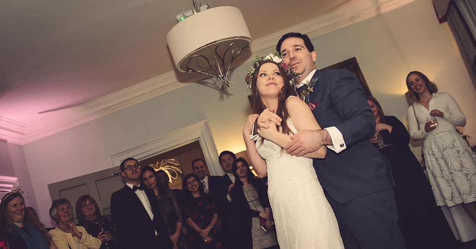 The bride and groom enjoy their first dance as their guests look on at their winter wedding at Morden Hall in London