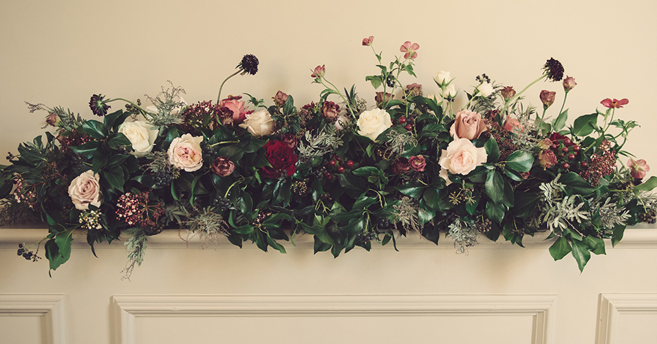 The venue was decorated with pale pink and deep burgundy roses with lots of seasonal foliage at this country house wedding in London