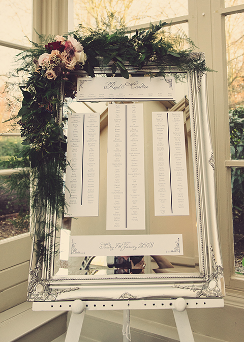 The table plan was displayed on an elegant silver framed mirror decorated with winter wedding flowers at Morden Hall in London