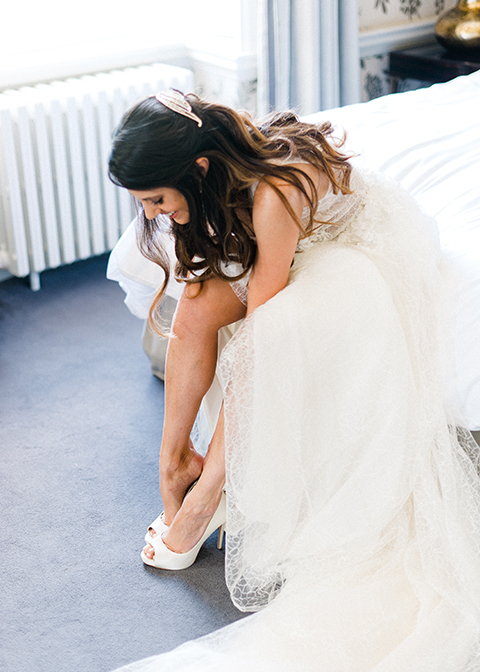 The bride makes the final touches to her outfit in the bridal preparation room at Morden Hall in London