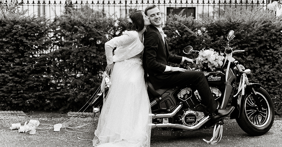 The bride and groom have a photo with the groom's classic motorbike at this wedding at Morden Hall