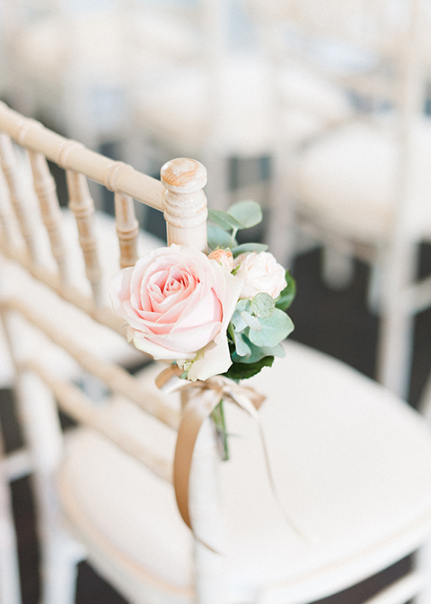 Pretty pink roses were tied to wedding ceremony chairs at this London Wedding Venue