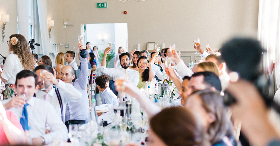 The wedding guests raise a glass to the happy couple at this country house wedding in London