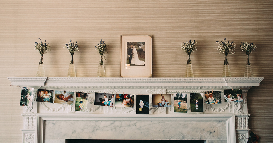 The fireplace was decorated with petite vases of flowers and family photographs at Morden Hall in London