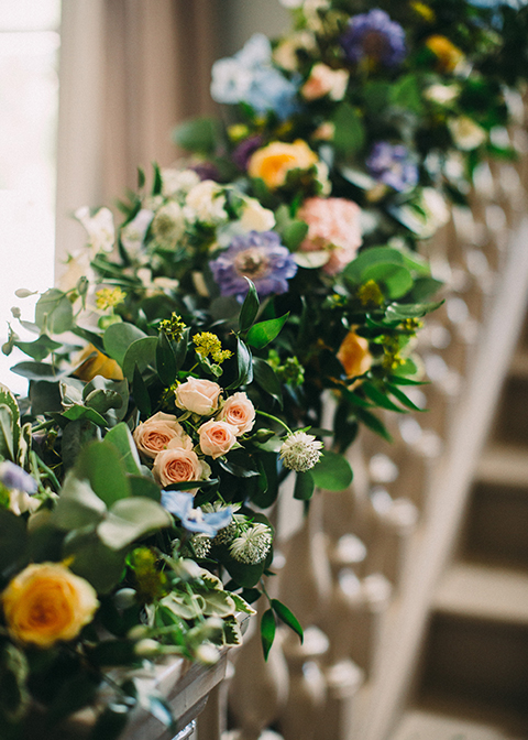 The staircase was decorated with garlands of beautiful summer wedding flowers at Morden Hall in London
