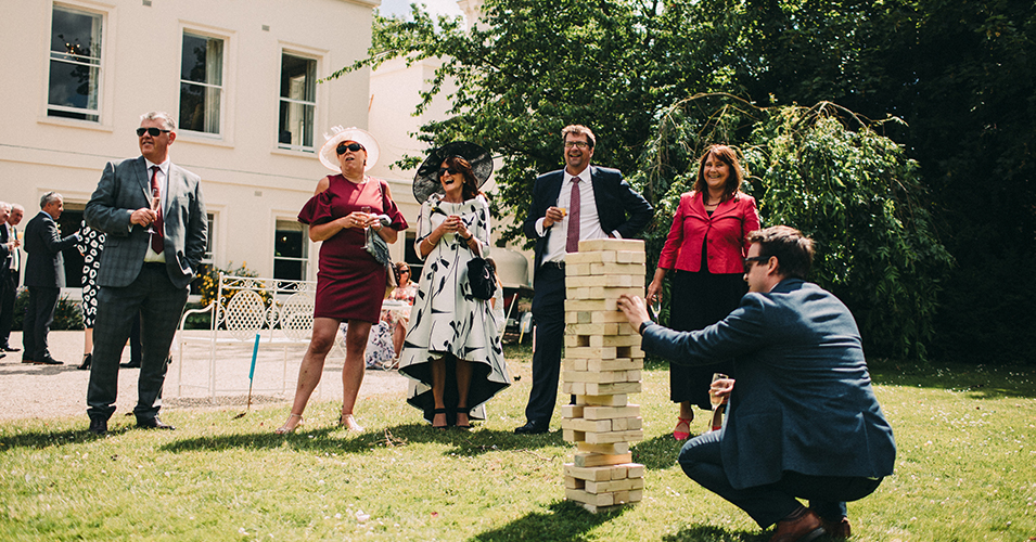 The guests enjoy a game of Jenga in the gardens at this summer wedding at Morden Hall