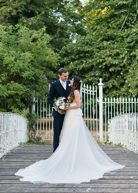 The happy couple pose for a photo on the bridge at Morden Hall in London