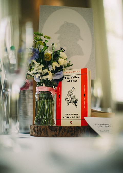 Story books and vases of pretty summer wedding flowers displayed on log slices were used as centrepieces at this summer wedding at Morden Hall